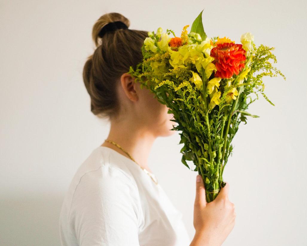 Frau mit Blumenstrauss im Gesicht
